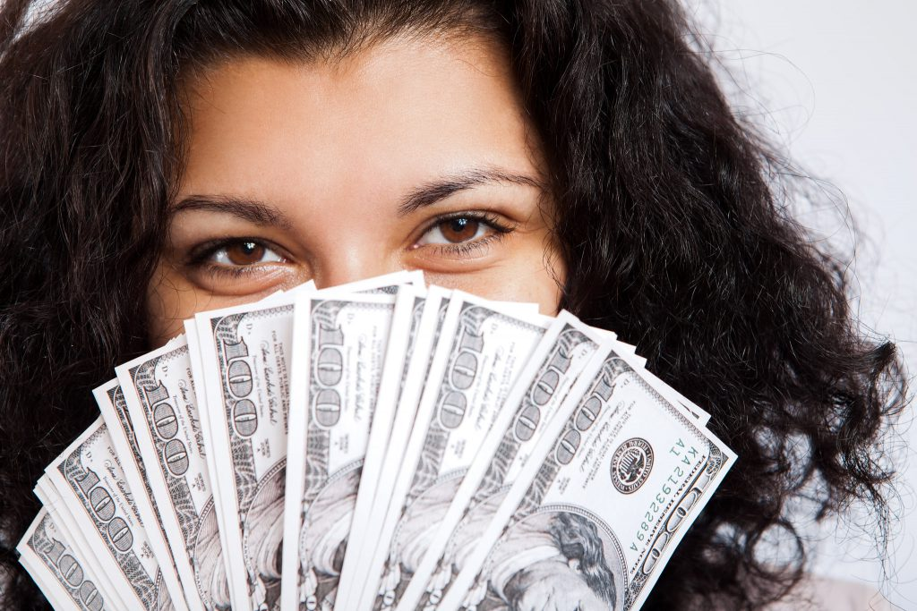 Cam girl face covered with money bills